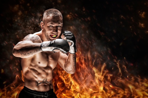 Artista das artes marciais mistas posando num contexto de fogo e fumaça. conceito de mma, boxe tailandês, boxe clássico. mídia mista