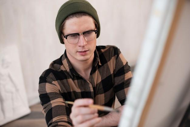 Artista de alto ângulo homem pintura sobre tela