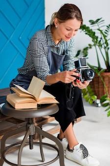 Artista de avental segurando câmera retro