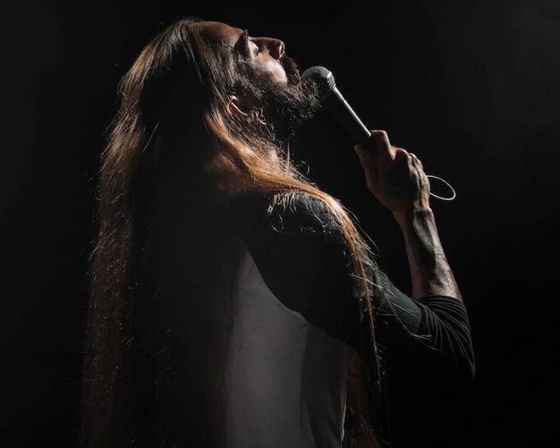 Artista de cabelo comprido segurando um microfone no palco