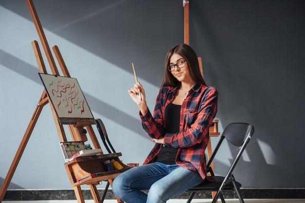 Artista de cabelos escuros, segurando um pincel na mão e desenha uma imagem sobre tela.