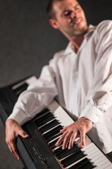 Artista de camisa branca segurando e tocando piano digital