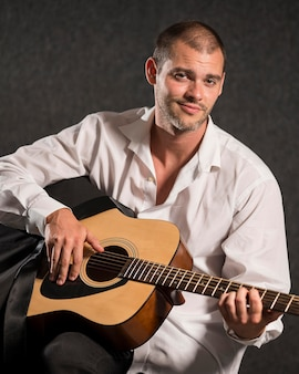 Artista de camisa branca sorrindo e tocando violão