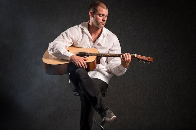 Artista de camisa branca tocando violão de longo alcance