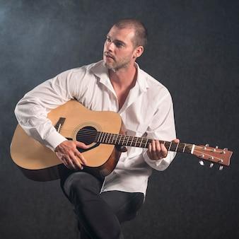 Artista de camisa branca tocando violão e desviando o olhar