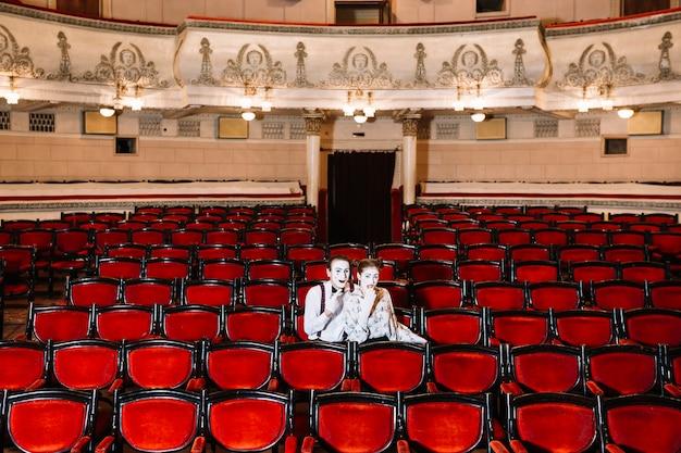 Artista de casal mime sentados juntos na cadeira no auditório