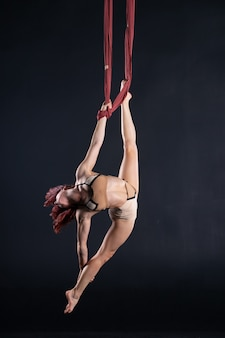 Artista de circo aéreo atlética, sexy e flexível feminina com a ruiva dançando no ar na seda.