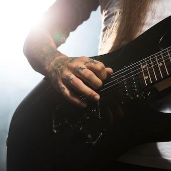 Artista de close tocando guitarra