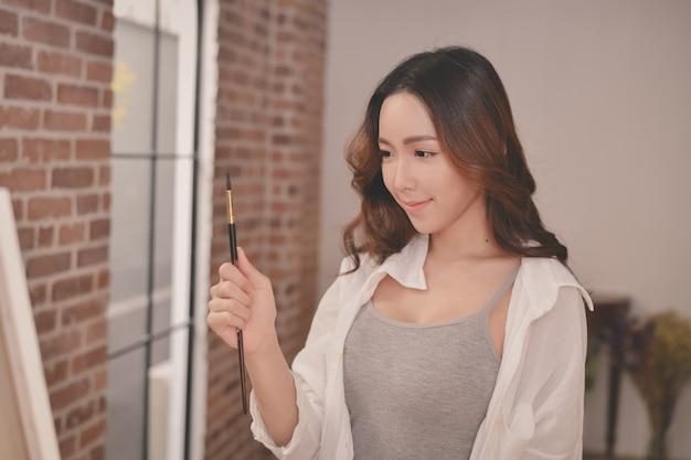 Artista de conceito linda garota. jovem artista pintando na galeria.