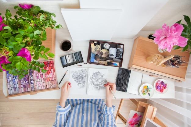Artista de garota de vista superior desenha um esboço de flores de rosa mosqueta sentado em seu local de trabalho com buquês de flores e materiais para criatividade. conceito de hobby e criação