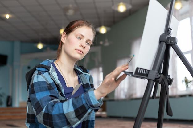 Artista de garota no processo de desenhar pinturas a óleo.