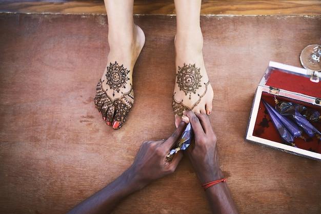 Artista de henna (mehndi) pintando o pé das mulheres no dia do casamento indiano