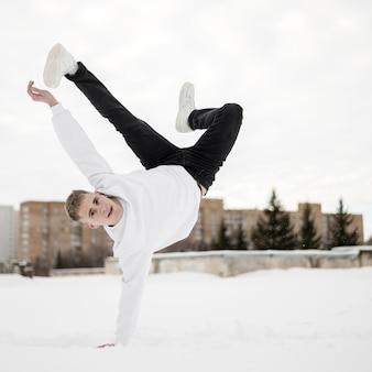 Artista de hip-hop masculino dançando lá fora na neve