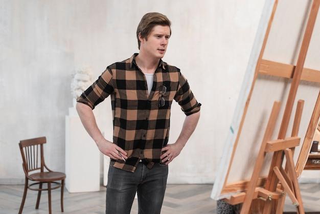 Artista de homem tiro médio olhando para sua pintura
