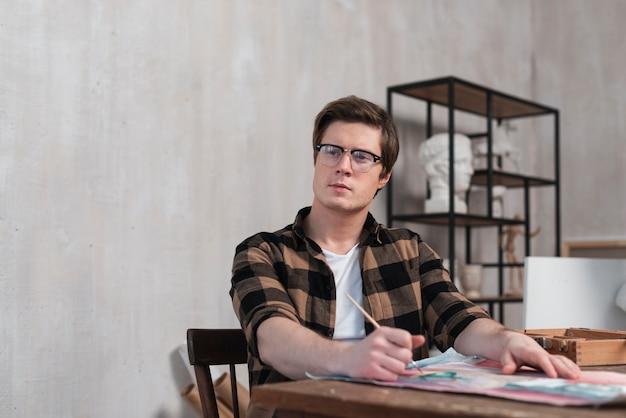 Artista de homem vista frontal pensando sobre o que pintar com espaço de cópia