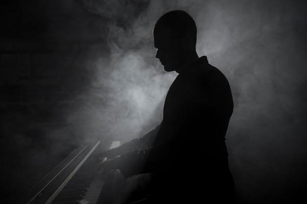 Artista de lado tocando fumaça de piano e efeitos de sombras