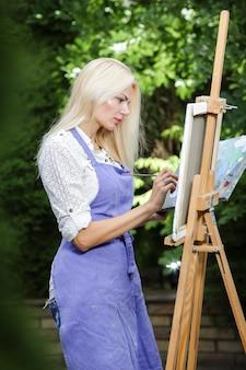Artista de linda mulher loira com um pincel na mão desenha na tela na natureza.