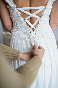 Artista de make-up ajuda a noiva amarrar seu vestido de noiva
