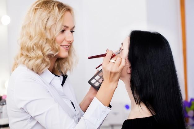 Artista de make-up, fazendo a garota de maquiagem no salão, conceito de beleza