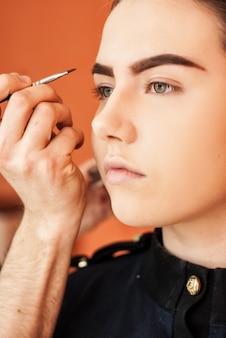 Artista de make-up fazendo maquiagem de uma linda jovem no estúdio