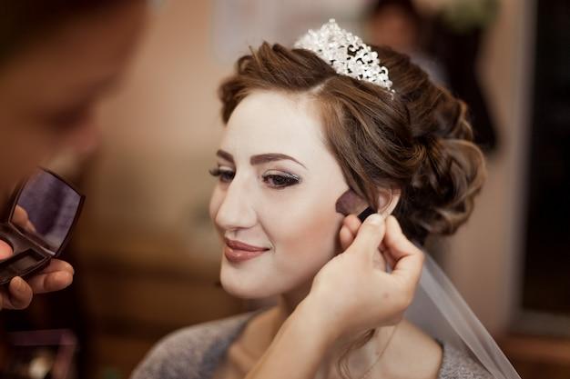 Artista de make-up, fazendo maquiagem para a noiva no dia do casamento.