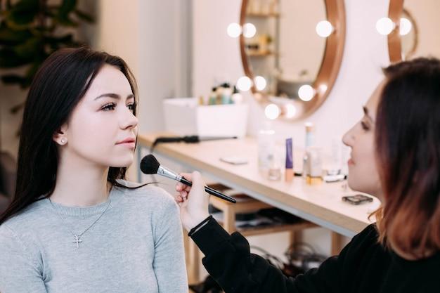 Artista de maquiagem admira seu modelo sentado diante do espelho