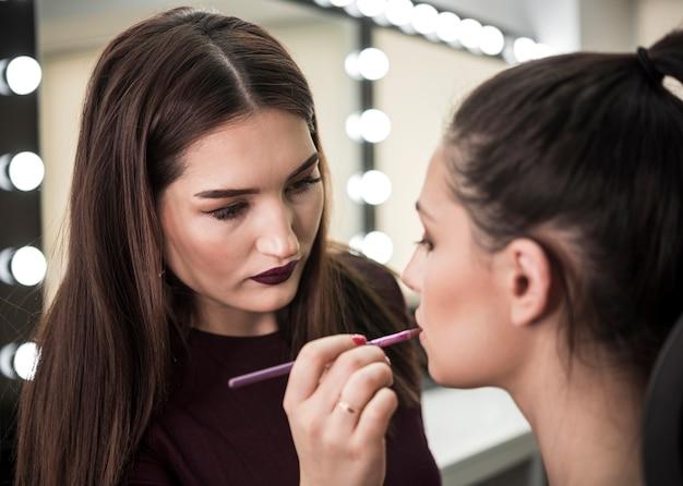 Artista de maquiagem aplicando batom