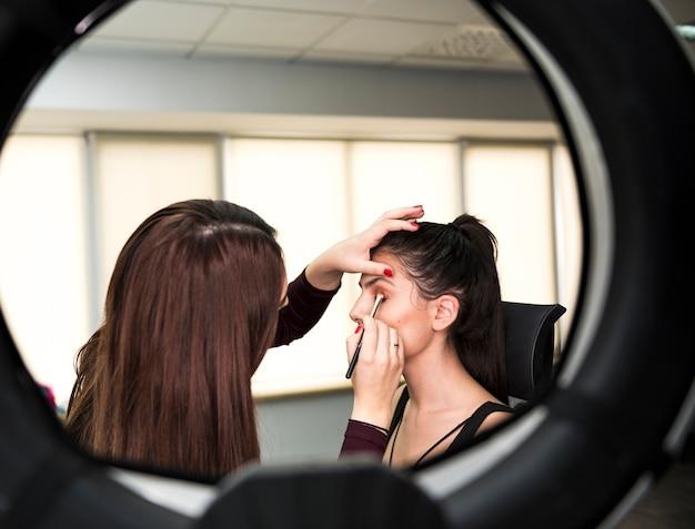 Artista de maquiagem aplicando maquiagem