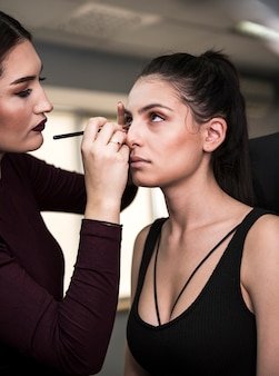 Artista de maquiagem aplicando sombra nos olhos