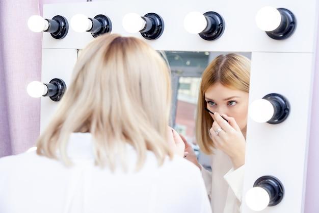Artista de maquiagem bonita olha o reflexo no espelho e aplica o rímel de chicote preto