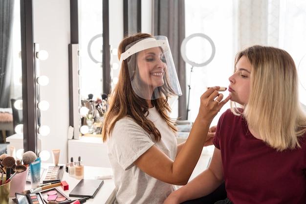 Artista de maquiagem com protetor facial passando batom na cliente