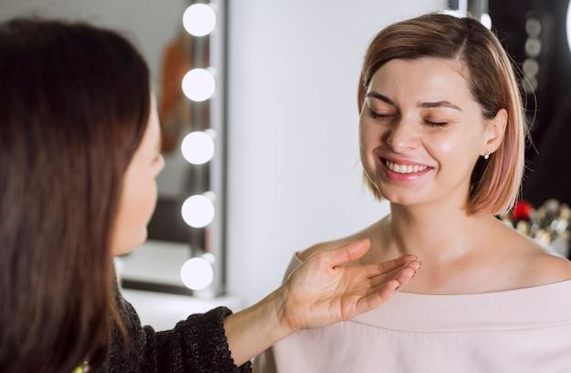 Artista de maquiagem fazendo cliente rir