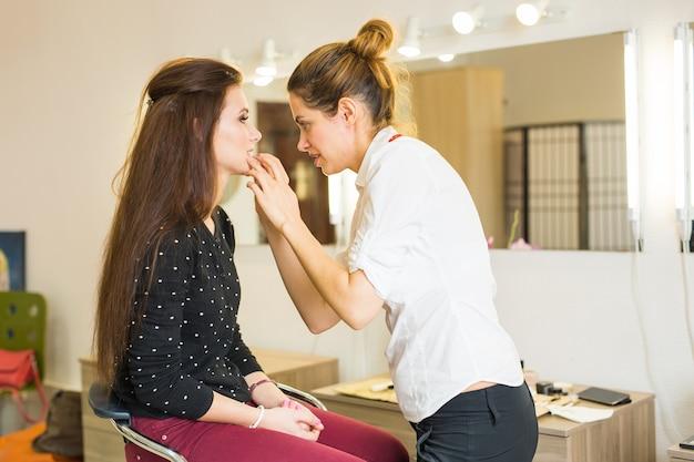 Artista de maquiagem fazendo maquiagem linda garota no salão, conceito de beleza e estilo.