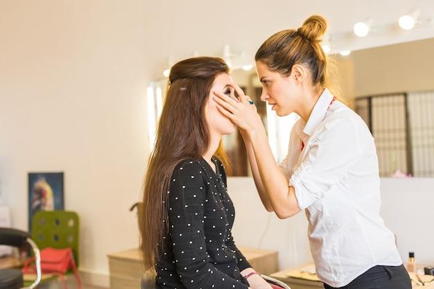 Artista de maquiagem fazendo maquiagem profissional em uma jovem