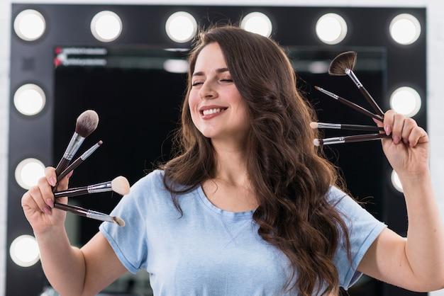 Artista de maquiagem mulher feliz com pincéis nas mãos