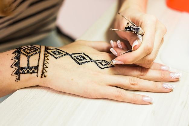 Artista de mehendi jovem pintando henna na mão.