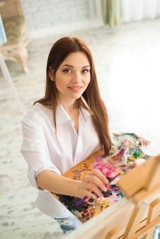 Artista de menina linda pinta sobre tela sobre o cavalete. modelo no estúdio