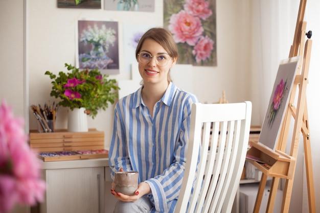 Artista de menina sorridente linda caucasiana com óculos tintas em estúdio em casa em fundo de flores cor de rosa e pinturas na parede com habilidade para criatividade. conceito de criatividade e inspiração