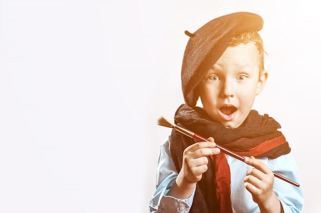 Artista de menino em boina preta, cachecol e com um pincel na boca