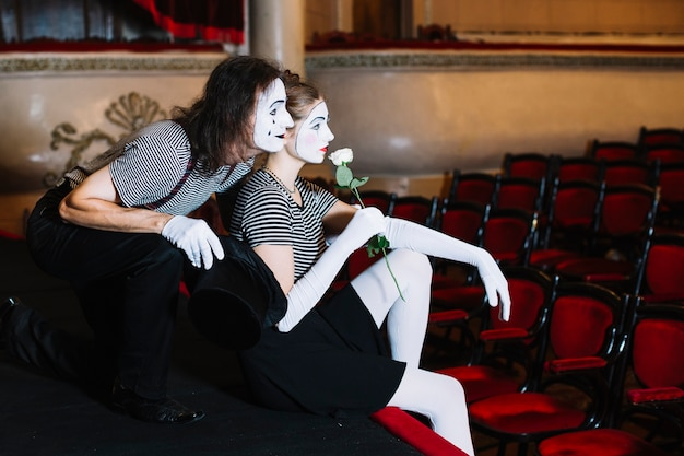 Artista de mímica de casal contemplado sentado no palco no auditório