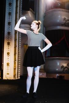 Artista de mímica feminina em pé no palco, flexionando seu músculo no auditório