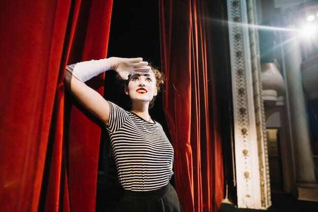 Artista de mímica feminina em pé perto da cortina vermelha, protegendo os olhos
