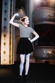 Artista de mímica feminina no palco flexionando seu músculo