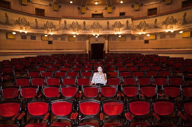 Artista de mímica feminina sentada sozinha em um auditório
