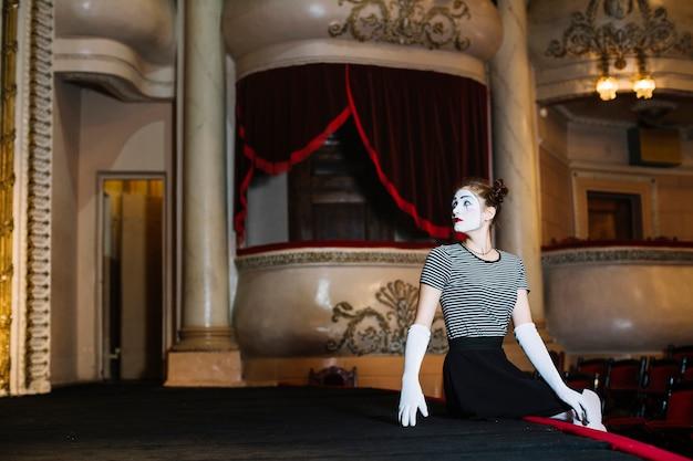 Artista de mímica feminina sentado à beira do palco no auditório