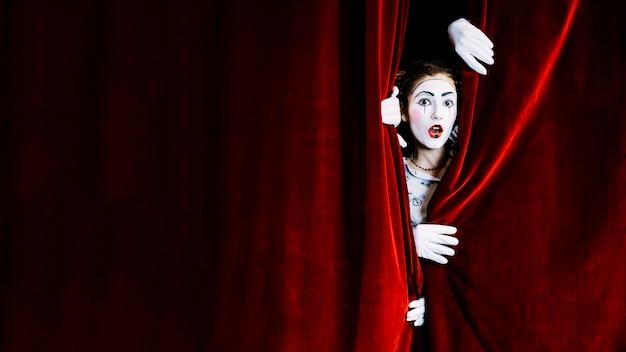 Artista de mímica feminino chocado, espreitando da cortina vermelha