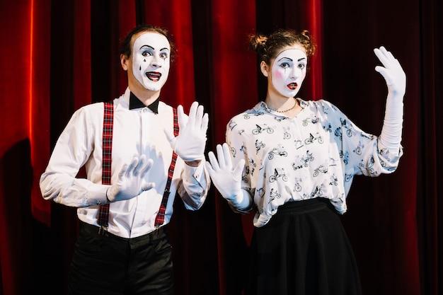 Artista de mímica masculina e feminina em frente a cortina vermelha, mostrando o gesto com a mão