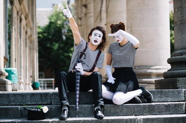 Artista de mímica masculina e feminina gesticulando enquanto está sentado na escada