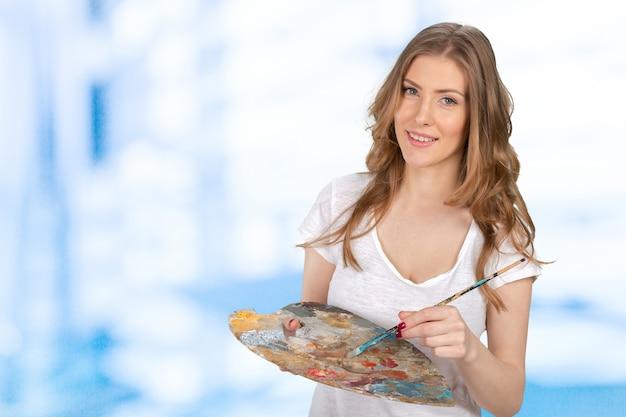 Artista de mulher bonita jovem holing pincel e paleta