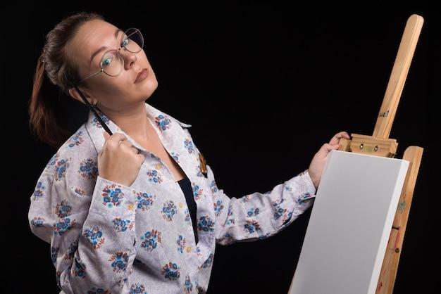 Artista de mulher com pincel e tintas nas mãos fica perto do cavalete e olha para a câmera.